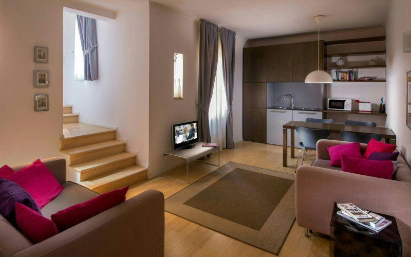 hotel-anahi-rome-apartment-armchairs-table-tv-stairs-kitchen-corner-54